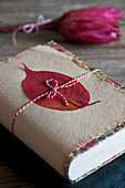 Book gift wrapped with autumn leaf on handmade paper