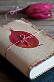 Buchgeschenk verpackt mit Herbstblatt auf geschöpftem Papier