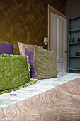 Bedspread and scatter cushions on bed in bedroom with patterned wallpaper