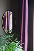 View across potted palm to mirror on wall next to purple curtain
