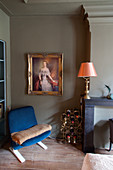 Blue easy chair, gilt-framed mirror and wine rack in bedroom