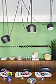 Elegant walnut table, pendant lamps and sideboard in dining room with green accent wall