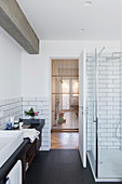 Washstand and glass shower cubicle in bathroom with subway tiles