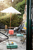 Loungers, parasol and bistro table on stone terrace