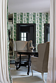 Round, antique wooden table and armchairs in room with botanical wallpaper