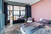 Double bed in bedroom with industrial door leading into living room