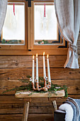 Advent arrangement of four tapered candles in copper-pipe candle holder