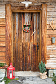 Rustic front door of wooden house decorated with lantern, conifer and wreath