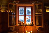 Winterliche Deko mit Engeln und Kerzen am ländlichen Fenster