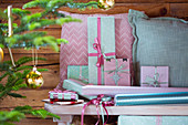Wrapped gifts and cushions in pink and mint-green on bench