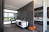 Freistehende Badewanne mit modernen Bad mit verspiegelter Wand