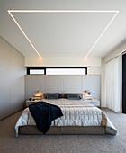 Modernes Schlafzimmer in Hellgrau mit eingelassener Deckenleuchte