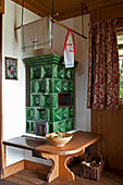 Classic green tiled stove with bench in rustic country house
