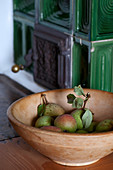 Pears in wooden bowl on bench around green tiled stove
