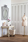 Console table and tailors' dummy in front of fitted cupboards