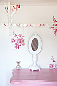 White vanity mirror on pink cabinet