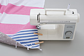 Sewing striped cloth and oilcloth backing together