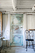 Two ornate metal chairs flanking battered panelled door in wooden house