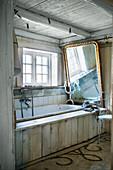 Large gilt-framed mirror above bathtub in rustic bathroom