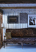 Antique Baroque sofa against board wall in rustic wooden house