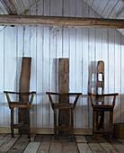 Drei Stühle aus altem Holz vor Bretterwand im Holzhaus