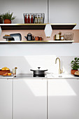 A white kitchen counter with an open shelf above it and pendant lamp hanging from the ceiling