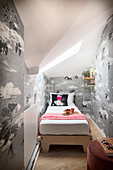 A narrow guest room with a single bed and monochrome wallpaper