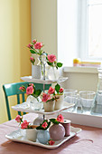 DIY cake stand decorated with roses in small vases
