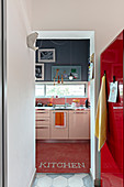 Looking along a red refrigerator into a kitchen with a window strip