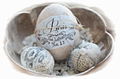 Easter eggs decorated with magazine clippings in silver bowl