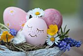 Topf als Osternest, Osterei mit Gesicht, Gänseblümchen, Butterblumen, Traubenhyazinthe und Feder als Deko