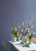 Handmade Easter decorations made from wooden bead on branches in vases