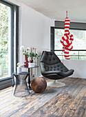 Sitzecke mit schwarzem Sessel, Beistelltisch und rot-weiß gestreiftem Dekoobjekt