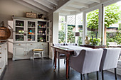 Upholstered chairs at a wooden table in a dining room with a conservatory