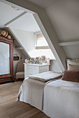 A classic attic bedroom with a gable window