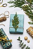 Weihnachtlich verpacktes Geschenk mit Thujazweig als Deko