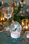 Weiße Maus in einer Schneekugel auf weihnachtlich gedecktem Tisch