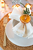 Napkin decorated with dried orange slice and juniper twig
