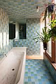 Wood grain bathtub in bathroom with blue and green tiles