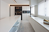 Island counter in white modern kitchen with marble floor
