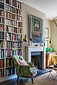 A floor-to-ceiling bookcase, an upholstered armchair and a modern work of art over the fireplace