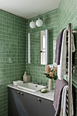 Greeen tiled bathroom with wall mounted cabinet