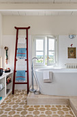 A towel rack next to a freestanding bathtub in an eclectic bathroom
