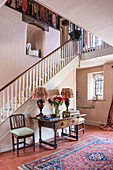 An antique table with chairs against a staircase wall in a entrance area