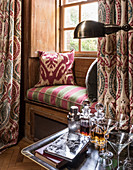 A 1930s Art Deco-style window seat and curtains with decanters and books in the foreground