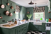 Green paint and copper pots on the wall in 1930s Art Deco-style kitchen