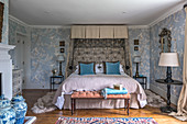 A double bed in a bedroom with 1930s Art Deco-style chinoiserie wallpaper