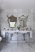 Decorative 1930s Art Deco-style mirrors above double sinks in a marble bathroom