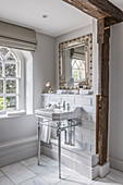 A sink and a silver framed mirror in a 1930s Art Deco-style bathroom