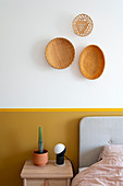 Arrangement of three baskets on wall above yellow-painted dado